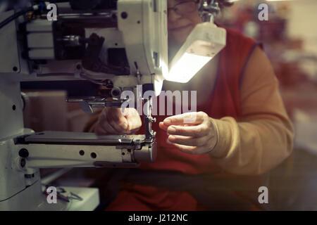 Frau arbeitet in der nähenden Industrie auf Maschine - Stockfoto