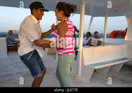 Touristen tanzen und Spaß auf einem See bei Sonnenuntergang Katamaran an der Westküste der Insel Aruba in der Karibik - Stockfoto