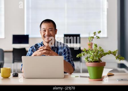 Lächelnde junge asiatische Designer bei der Arbeit in einem modernen Büro - Stockfoto