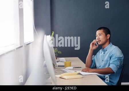 Junge asiatische Unternehmer sprechen auf einem Handy in einem Büro - Stockfoto