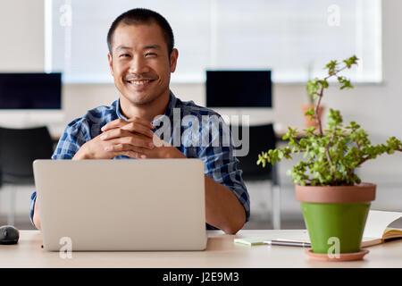 Glücklichen jungen asiatischen Unternehmer bei der Arbeit in einem modernen Büro - Stockfoto