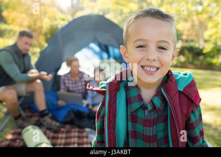 Junge lächelnd in die Kamera während der Familie sitzt am Zelt im Hintergrund an einem sonnigen Tag - Stockfoto