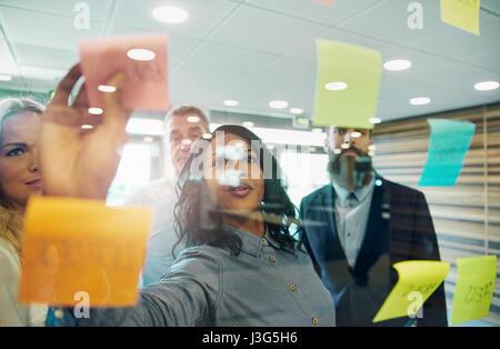 Geschäftsfrau, Haftnotiz auf Glas, Gruppe von Kollegen hinter ihr - Stockfoto