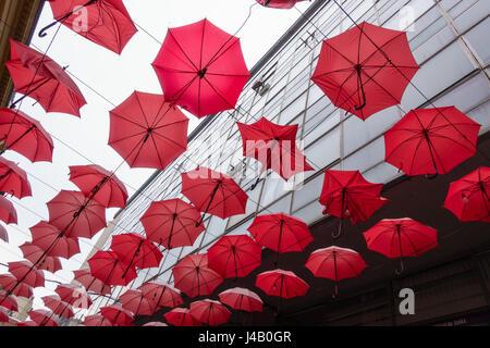Viele rote Sonnenschirme hängen in einer Reihen bis in den Himmel. - Stockfoto
