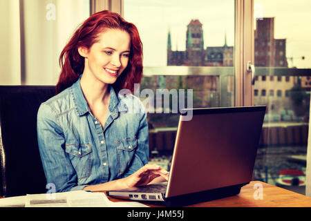 Rothaarige junge Business Frau oder Student Mädchen Arbeit mit Dokumenten und Laptop in der Nähe von Fenster. Business - Stockfoto