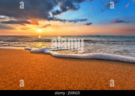 Magischen Sonnenaufgang über dem Meer. Goldstrand und dramatischen Himmel. - Stockfoto
