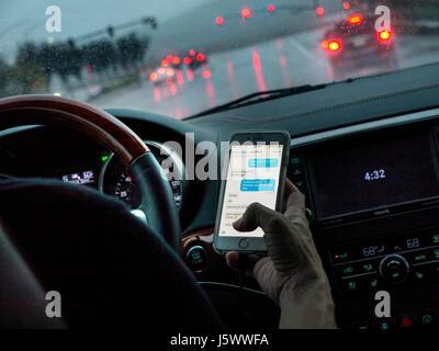 Fahrerin in l/h Fahrzeug heimlich SMS mit iPhone Smartphone während der Fahrt auf belebten nassen Straße bei Dämmerung - Stockfoto
