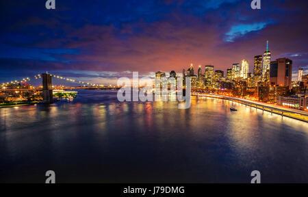 Skyline von New York City. Blick zur Broklyn Bridge über den East River und Manhattan bei Nacht - Stockfoto