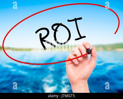 Hand des Mannes ROI (Return on Investment) mit schwarzem Filzstift auf Bildschirm zu schreiben. Auf Hintergrund - Stockfoto