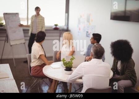 Kollegen betrachten Geschäftsmann hält Vortrag in Kreativbüro - Stockfoto
