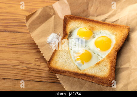 frittierte Wachteleier in einem Toast auf hölzernen Hintergrund - Stockfoto