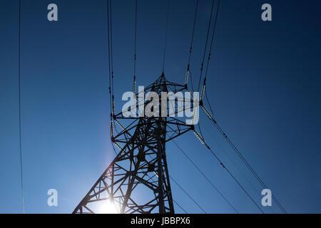 Hochspannungsmasten macht gegen blauen Himmel und Sonne Strahlen, Hochspannungs-Leitungen bei Sonnenaufgang. - Stockfoto