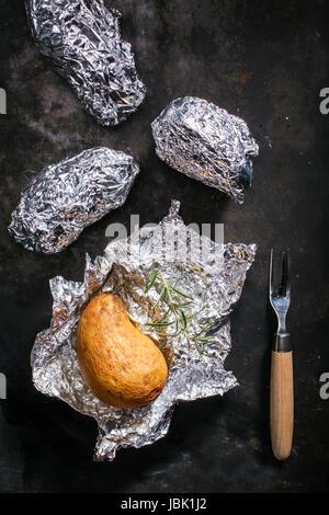 Kartoffeln gebraten in ihrer Haut in Alufolie auf ein Sommer BBQ ausgepackt, für eine leckere Begleitung zu einer - Stockfoto