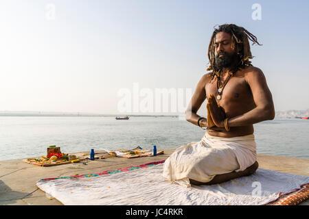 Ein sadhu, heiliger Mann, sitzt und Beten auf einer Plattform am heiligen Fluss Ganges Meer Ghat im Vorort godowlia - Stockfoto