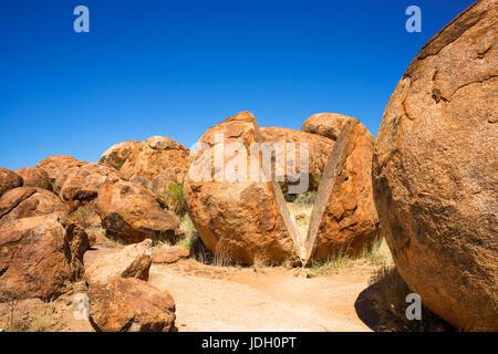 Devils Marbles - Felsen aus rotem Granit sind auf Grundgestein, Australien, Northern Territory ausgeglichen. - Stockfoto