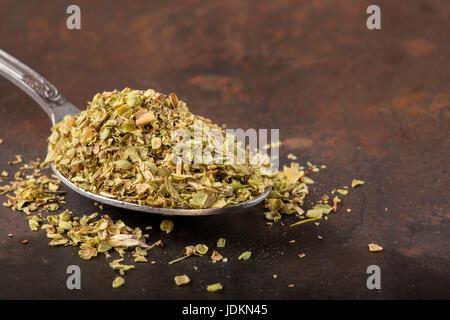 Löffel gefüllt mit getrockneten Oregano auf rostigen Hintergrund - Stockfoto