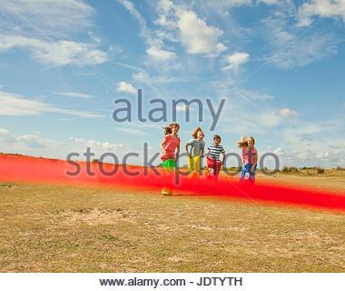 Kinder mit Sackhüpfen auf Strand - Stockfoto