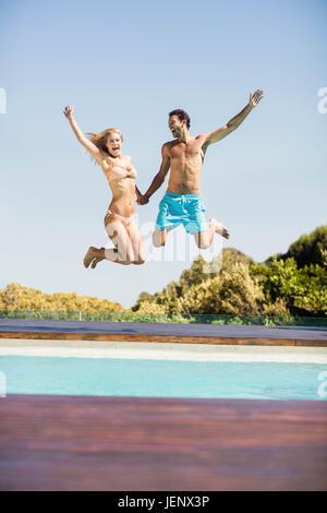 Glückliches Paar in den Pool springen - Stockfoto