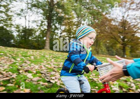 Kleiner Junge mit seinem Fuß Fahrrad in Richtung arme Mutter in Herbstlandschaft fahren - Stockfoto