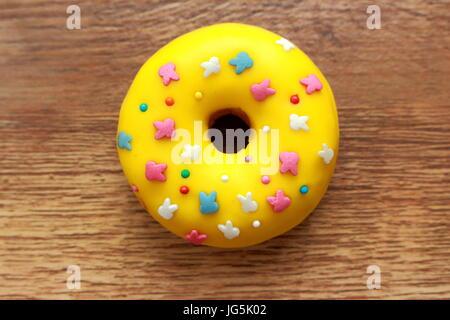 Einzelne gelbe Donut auf Holz Hintergrund - Stockfoto