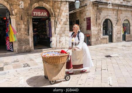 Kroatien-Dubrovnik Kroatien Frau gekleidet in traditioneller kroatischer Tracht mit Souvenirs auf der Placa Haupt - Stockfoto