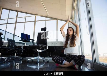 Junge Geschäftsfrau mit Augen geschlossen beim Yoga im Stock im Büro - Stockfoto