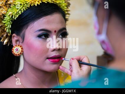Eine Frau beim Schminken, ein junges Mädchen in Tracht vor einen Zahn Einreichung Zeremonie, Insel Bali, Canggu, - Stockfoto