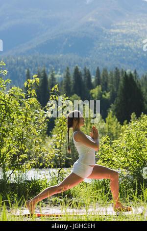 Frau tut Yoga-Pose auf Matte im Wald an einem sonnigen Tag - Stockfoto