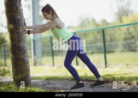 Seite Blick voller Länge der junge Frau in Sportkleidung Ausübung von Baum - Stockfoto