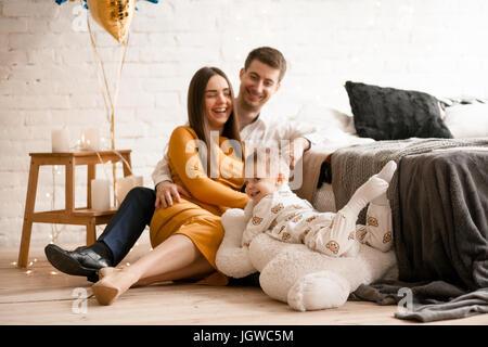 Eltern in der Nähe von Bett sitzen und spielen Sie mit ihrem Kleinkind. Glückliche junge Familie zusammen. - Stockfoto