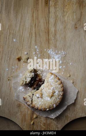 Overhead Schuss eines teilweise gegessen Weihnachten Mince Pie bröckelt Gebäck mit Puderzucker, auf einem alten - Stockfoto