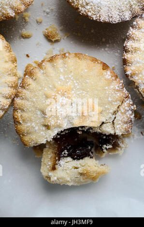 Overhead Nahaufnahme von einem Mince Pie in einer Gruppe, aufgebrochen als ob teilweise gegessen.  Weiße Glasur - Stockfoto