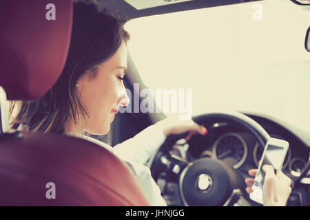 Schöne Geschäftsfrau SMS während der Fahrt zur Arbeit - Stockfoto