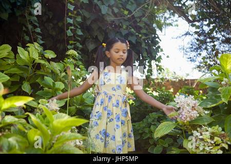 Mädchen stehen inmitten von grünen Pflanzen im Garten - Stockfoto