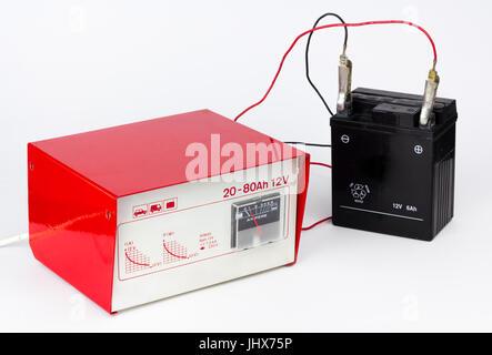 Roten Ladegerät angeschlossen an eine schwarze Motorradbatterie - Stockfoto