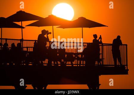 Aberystwyth Wales UK, Montag, 17. Juli 2017 UK Wetter: Menschen auf Aberystwyth Pier sind in den lebendigen goldenen - Stockfoto