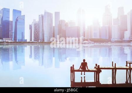 Traum Konzept, Mann auf dem Steg sitzen und genießen Sie modernen Stadtbild Skyline Blick - Stockfoto