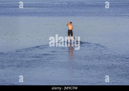 Mann auf Paddle Board paddeln, zum See - Stockfoto