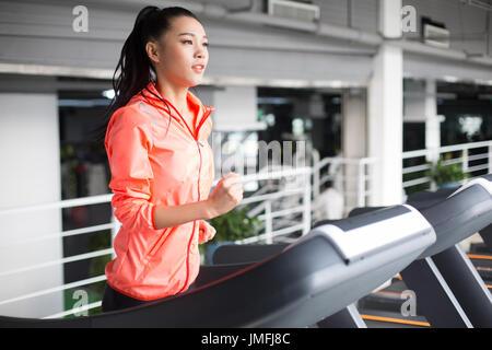 Junge Chinesin auf Laufband im Fitnessstudio - Stockfoto