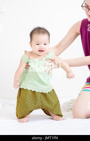 Entzückende Baby Babymädchen mit Hilfe der Mutter zu Hause laufen lernen - Stockfoto