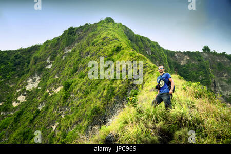 Ein junger Mann-Reisender Fuß entlang des oberen Randes einer Berg-Manta-Bucht, die Insel Nusa Penida auf grünem - Stockfoto