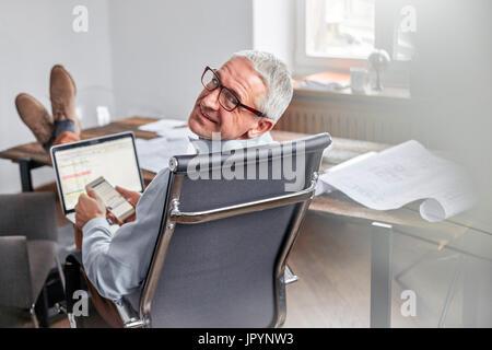Porträt lächelnd, zuversichtlich Geschäftsmann mit Handy und Laptop im Büro - Stockfoto