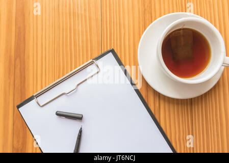 Eine Tasse Tee oder Kaffee und ein Stift und Notebook auf hölzernen Schreibtisch im Büro - Stockfoto