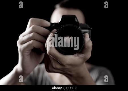 Nahaufnahme eines jungen kaukasischen Mann schießen Sie ein Foto mit einer Spiegelreflexkamera - Stockfoto