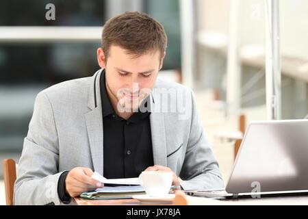 Konzentriert executive Lesen von Dokumenten in einem Café sitzen - Stockfoto