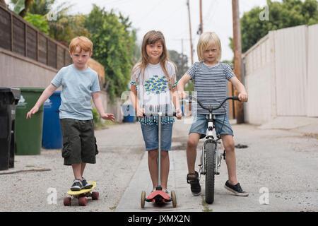 Mädchen und Jungen in der Gasse mit dem Motorroller, dem Fahrrad und Skateboard - Stockfoto