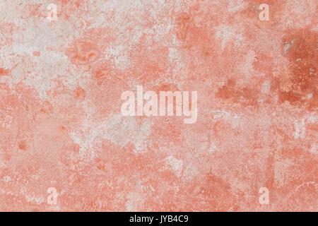 Nahaufnahme einer Verwitterten und gealterte Betonwand, gebleicht roter Farbe teilweise abgeblättert. Textur Hintergrund. - Stockfoto