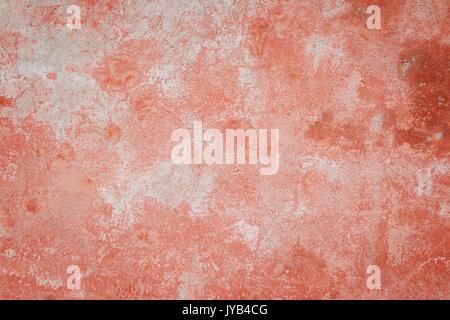 Nahaufnahme einer Verwitterten und gealterte Betonwand, gebleicht roter Farbe teilweise abgeblättert. Textur Hintergrund - Stockfoto