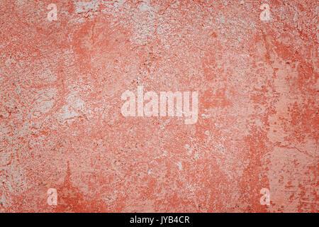 Nahaufnahme einer Verwitterten und gealterte Betonwand mit Gebleichtem rote Lackierung. Textur Hintergrund mit Vignettierung. - Stockfoto