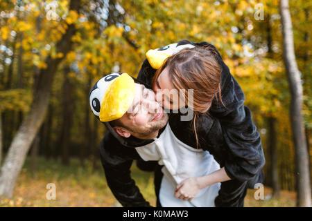 Paare, die in passenden Pinguin Schlafanzug im Herbst Wald - Stockfoto